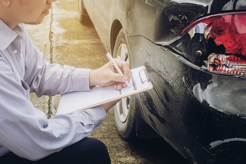 Man checking car for claim intimation after car accident